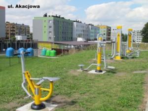 Siłownia zewnętrzna przy ul. Akacjowej w Ornontowicach. Zdjęcie wykonano w dzień, przedstawia ono urządzenia siłowni zewnętrznej w kolorze szaro-żółtym. W tle widać zabudowę wielorodzinną przy ul. Akacjowej. Elementy siłowni zewnętrznej stoją na zielonej trawie.