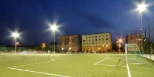 """Kompleks sportowy """"Moje Boisko – ORLIK 2012"""" ul. Akacjowa 1a. Na zdjęciu widać boisko do piłki nożnej z zieloną murawą wieczorową porą. Boisko oświetlone jest reflektorami  W tle widać bloki wielorodzinne znajdujące się przy ul. Akacjowej w Ornontowicach."""