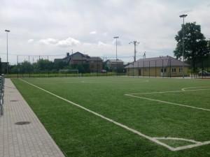 """Kompleks sportowy """"Moje Boisko – ORLIK 2012"""" ul. Okrężna 6. Na zdjęciu widać boisko do piłki nożnej z zieloną murawą w dzień. Po lewej stronie widać ławki przeznaczone dla publiczności, po prawej stronie w oddali widać budynek kompleksu sportowego, w którym znajdują się pomieszczenia gospodarcze oraz szatnie."""