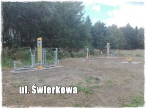 Siłownia zewnętrzna przy ul. Świerkowej w Ornontowicach. Zdjęcie wykonano w dzień, przedstawia ono urządzenia siłowni zewnętrznej w kolorze szaro-żółtym. W tle widać zielony las. Elementy siłowni zewnętrznej stoją na zielonej trawie.