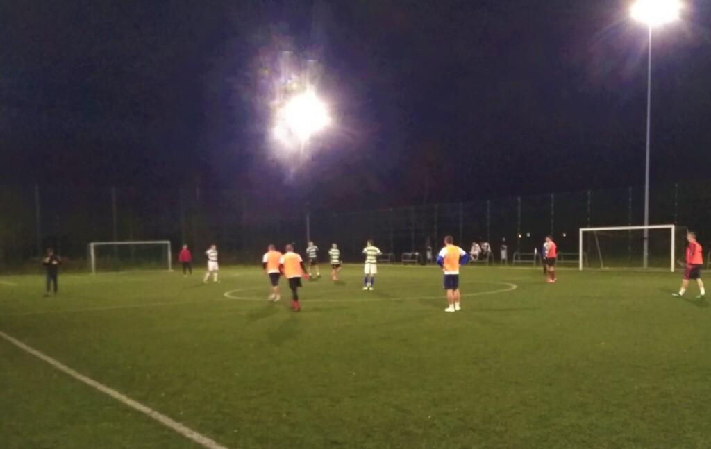 Zdjęcie przedstawia piłkarzy grających wieczorową porą na zielonej murawie w piłkę nożną. Boisko do piłki nożnej oświetlone jest reflektorami.