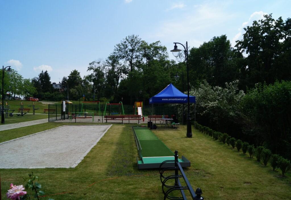 Zdjęcie wykonano w dzień. Na pierwszym planie widać pole do gry w minii golfa oraz boisko w grę w bule. W oddali widać plac zabaw. Po lewej stronie zdjęcia widać fragment siłowni zewnętrznej.
