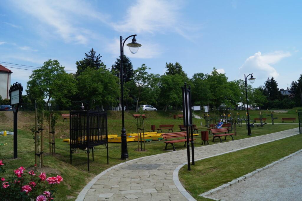 Zdjęcie wykonano w dzień. Na pierwszym planie widać alejkę prowadzącą przez kompleks rekreacyjny Bulodrom. Zdjęcie przedstawia ławeczki, na której odpoczywają ludzie. W oddali widać fragment siłowni zewnętrznej.