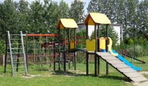 """Zdjęcie wykonano w dzień. Na zdjęciu widać zieloną trawę na którym stoi zestaw """"Ania"""" na który składa się drewniany podest do wejścia, zjeżdżalnię, metalowe drabinki, siatkę wykonaną z czerwonych lin oraz metalowe drążki do przejścia. Obok zestawu """"Ania"""" widać huśtawkę """"Ważka"""" dla dwójki dzieci. W oddali widać zielone drzewa, drewniany brązowy płot oraz biały jednorodzinny dom."""