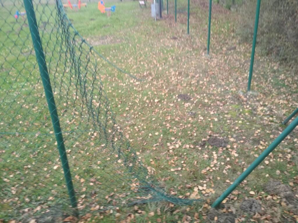 Zdjęcie uszkodzonego ogrodzenia przy placu zabaw.