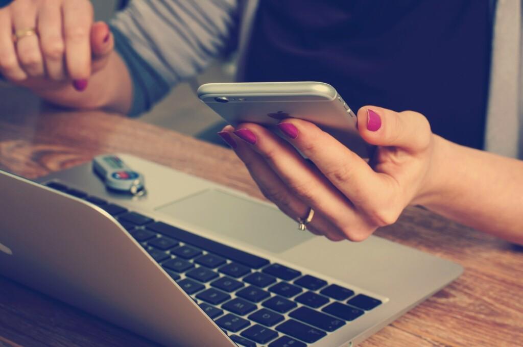 Zdjęcie laptopa i kobiety trzymającej w ręku telefon