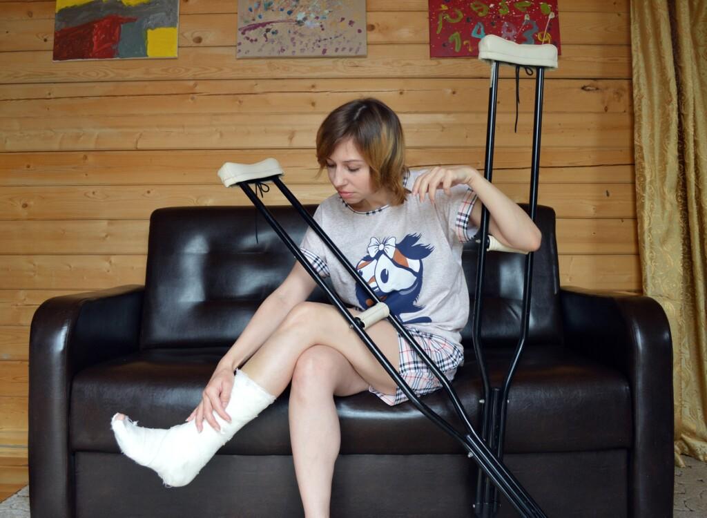 Zdjęcie kobiety z nogą w gipsie.